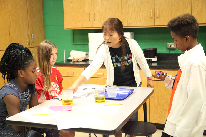 Ms. Rippeto helping students with science experiment