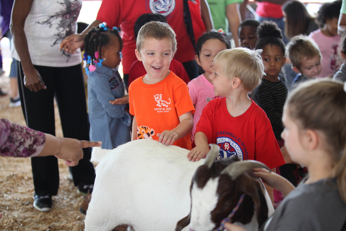 Two students petting a goat