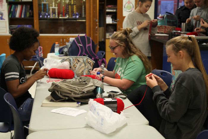 Advisory students knitting hats for American Heart Month