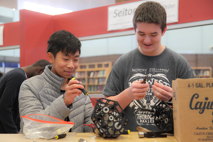 two students working on robotics club competition