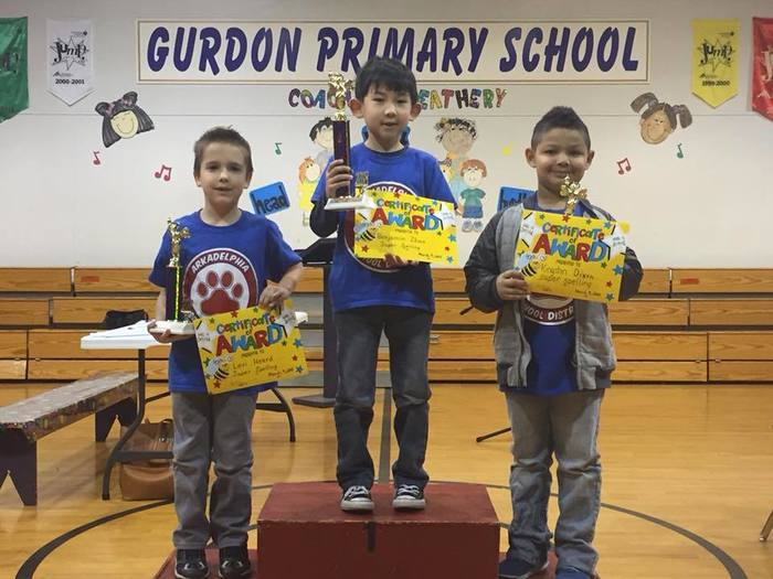 Three Perritt Primary students hold spelling bee trophy